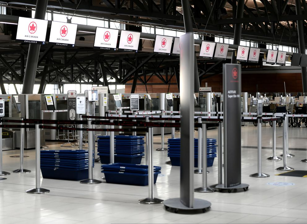 The Air Canada check-in area is deserted at Ottawa International Airport in Ottawa, Ontario, in the midst of the COVID-19 pandemic Saturday, May 16, 2020. (Justin Tang/The Canadian Press via AP)