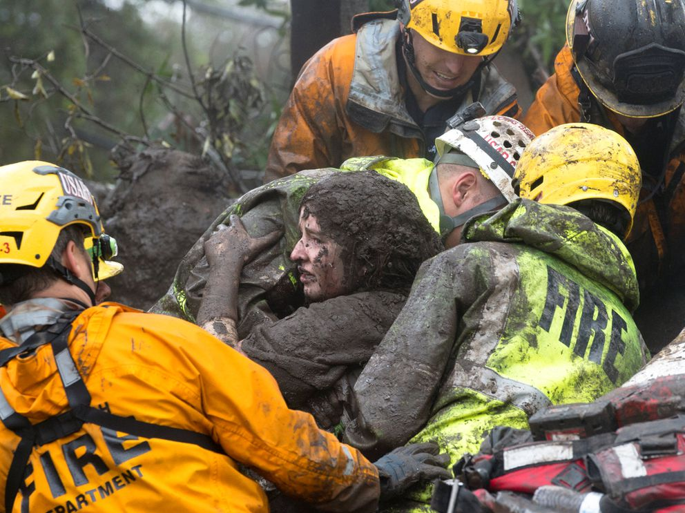 Emergency personnel carry a woman rescued from a collapsed house Tuesday after a mudslide in Montecito, California. Kenneth Song/Santa Barbara News-Press via REUTERS