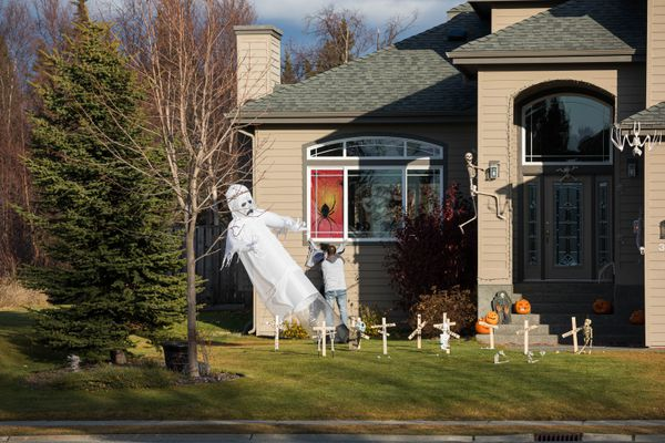 Patrick Hoogerhyde fixes a Halloween decoration in his yard on Wednesday, Oct. 30, 2019 in South Anchorage. (Loren Holmes / ADN)