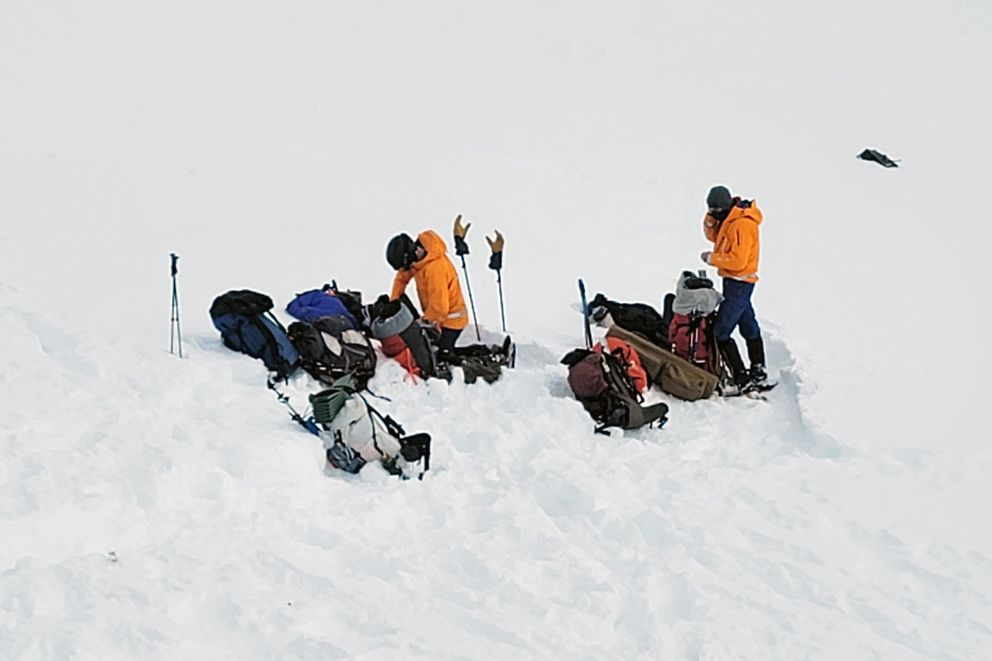 In this photo provided by the Alaska Mountain Rescue Group, some of the group's volunteers work near the scene of a helicopter crash close to the Knik Glacier in Alaska on Sunday, March 28, 2021. (Lance Flint/Alaska Mountain Rescue Group via AP)