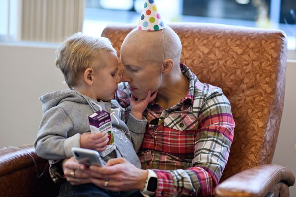 Wearing a party hat her mother brought her, Kikkan Randall hold her son, Breck, during her last full chemotherapy treatment at Katmai Oncology on October 22, 2018. Some chemotherapy will continue until spring 2019. (Marc Lester / ADN)
