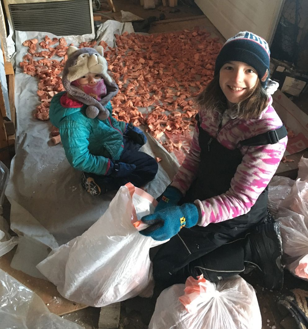 Olivia Schandelmeier, left, and her sister Jona help pack cut-up pork for mom Zoya Denure's 2020 Iditarod drops. The children worked in the family's garage near Paxson on a day when it was minus 40. (Photo by Zoya Denure)