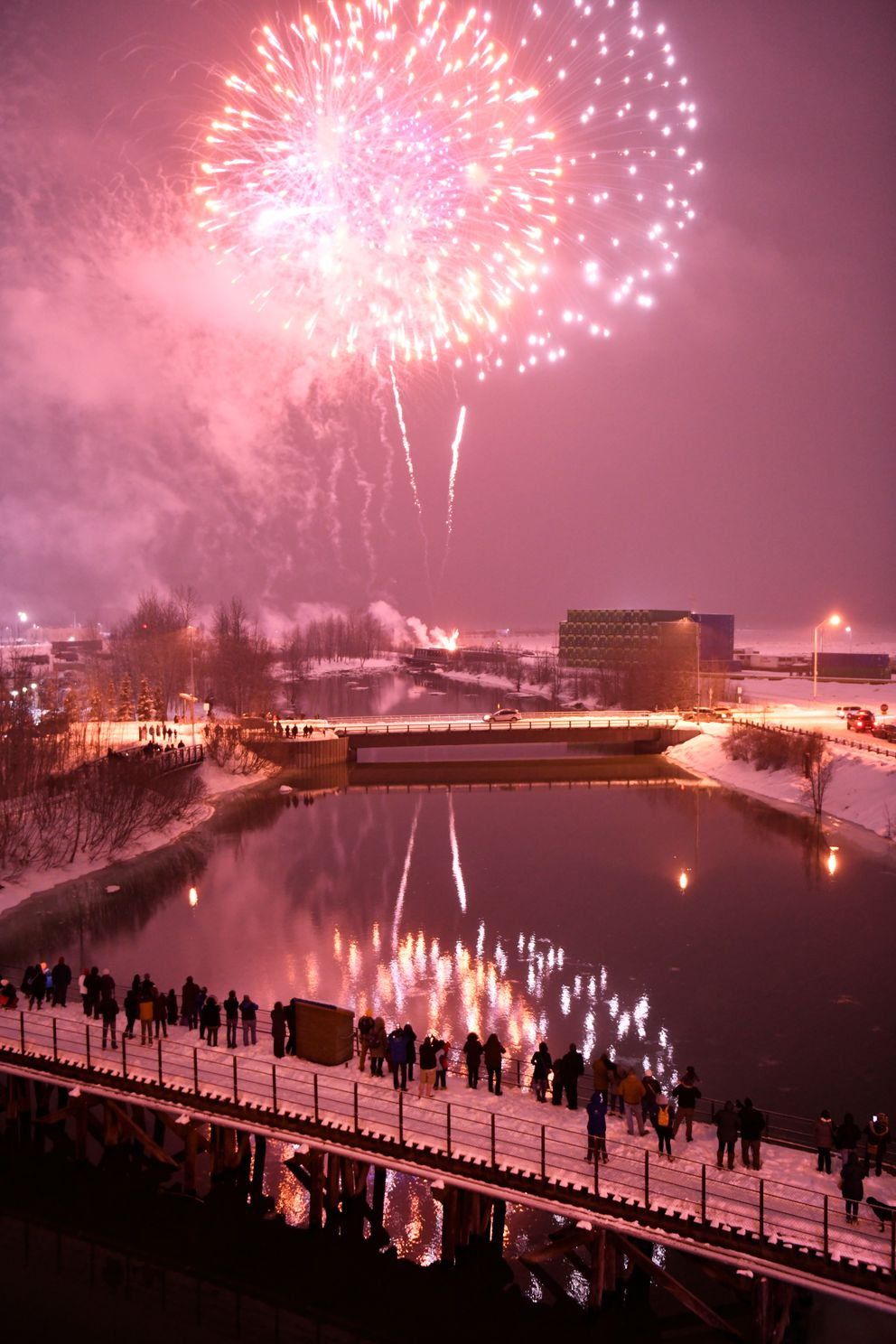 People watch the Fur Rondy fireworks from Ship Creek on February 27, 2021. (Marc Lester / ADN)