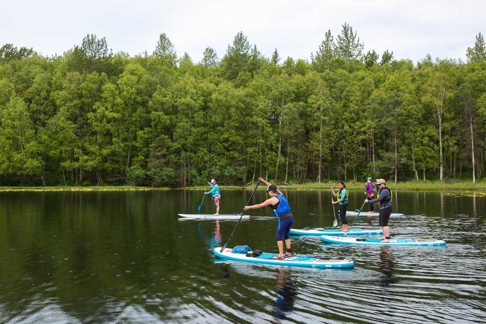 Alaska Wilderness SUP co-owner Jennah Jones, in blue, leads a paddleboard yoga group into Little Campbell Lake on Saturday, June 4, 2016. The new company started offering paddleboard yoga classes this summer. (Loren Holmes / Alaska Dispatch News)