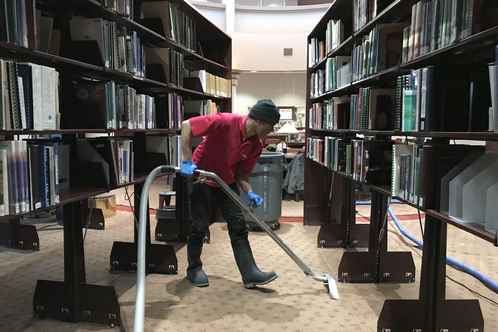 Nelson Alcequiez of Taylored Restoration vacuums up water from a burst heating pipe in the Alaska Collection at the Loussac Library on Tuesday. (Bill Roth / ADN)