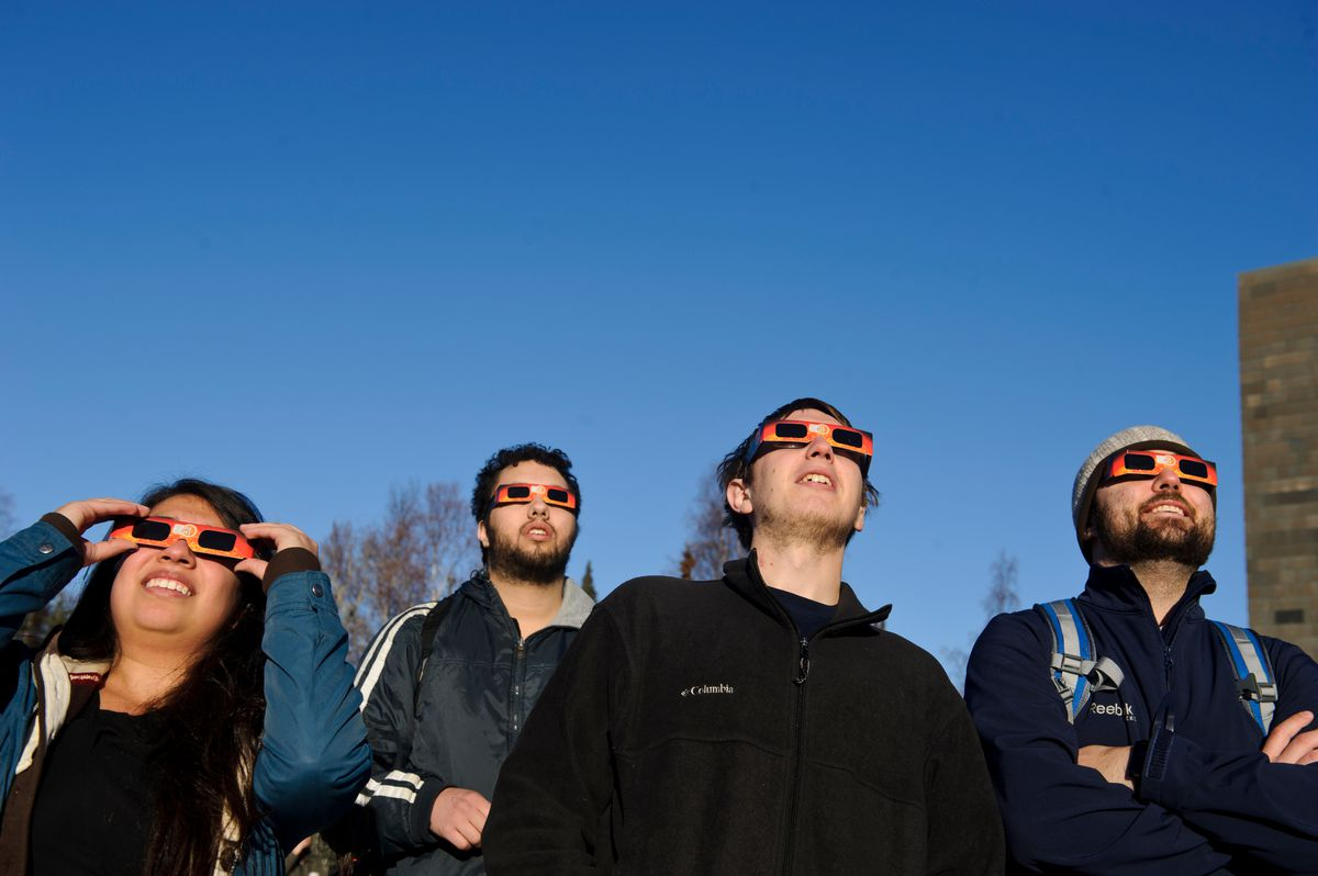 Students Ana Lambrano, Chris Peter, Ian Schacht and Jordan Couture look at the partial solar eclipse at UAA on Oct. 23, 2014. (Marc Lester / Alaska Dispatch News)