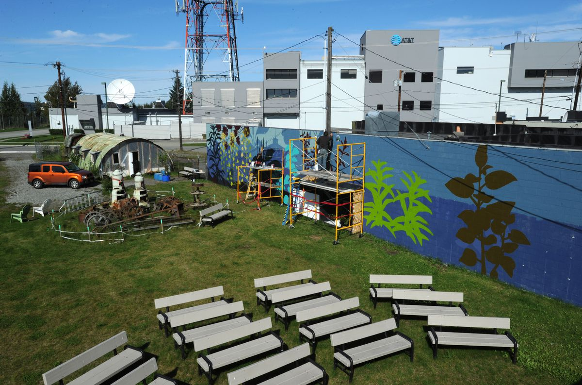 Artist Linda Infante Lyons of Anchorage, left, and her husband, artist Graham Dane, work from scaffolding as they paint a mural at the Government Hill Commons and community orchard on Wednesday, August 29, 2018. (Bill Roth / ADN)