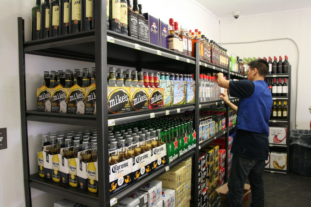 An Alaska Commercial Co. worker stocks the shelves of the AC liquor store in Bethel, Alaska, on opening day, Tuesday, May 3, 2016. The new liquor store, along with Fili's Pizza and its new beer and wine menu, offer the first legal sales of alcohol in Bethel in more than 40 years. (Lisa Demer / ADN)