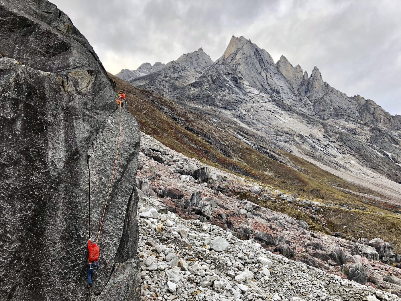 Andi Schweers, top, and Steven Claggett climb a boulder, featuring Caliban in the background, in the Arrigetch Peaks on Friday, Aug, 31, 2018. (Jussi Ruottinen)
