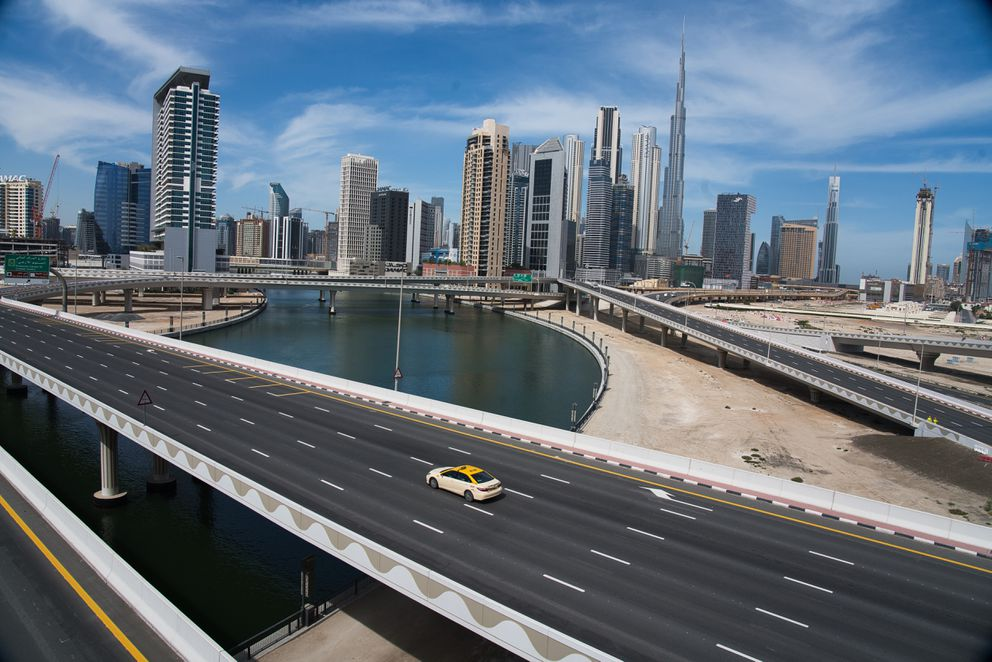 In this April 6, 2020, file photo, a lone taxi cab drives over a highway in front of the Dubai skyline. (AP Photo/Jon Gambrel, File)