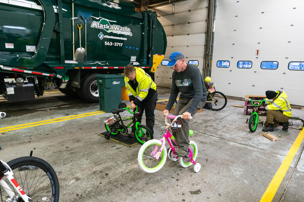 Alaska Waste driver John Clark does a wheelie to test a newly-built bicycle at Alaska Waste's bike build on Saturday. Alaska Waste employees started with a goal of raising enough money to purchase 20 bikes, and ended up with 77, which will be distributed to families in need through the Salvation Army. (Loren Holmes / ADN)
