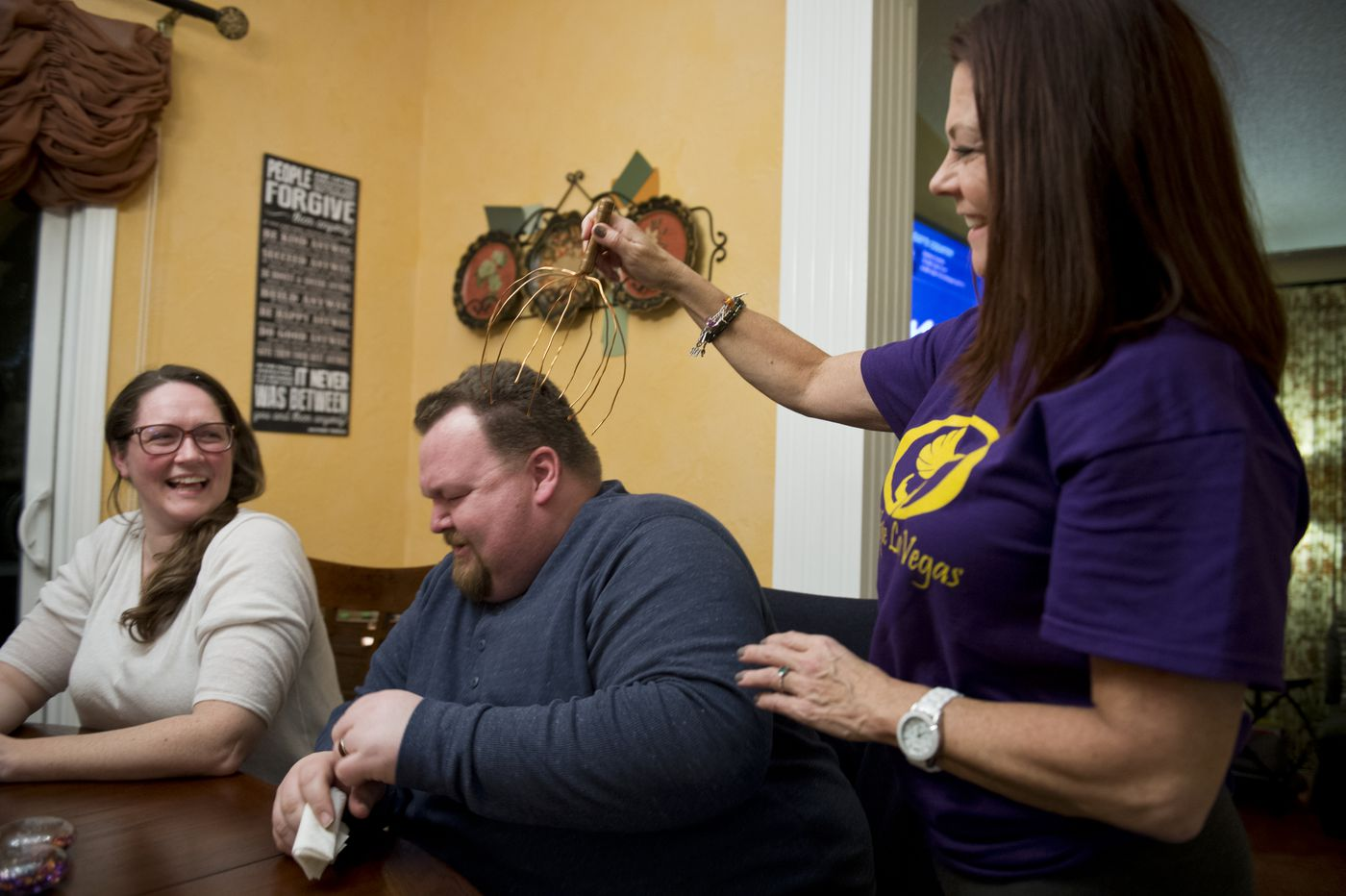 Erik Ross flinches as Jaimie Farrell uses a scalp massaging device on him during a dinner gathering on Dec. 1. Ross' wife, Chrissy Braniger, is at left. (Marc Lester / ADN)