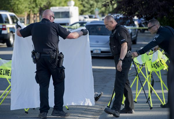 Anchorage Police limit the view of a body on Bliss Street as a shooting is investigated on July 20, 2018. (Marc Lester / ADN)