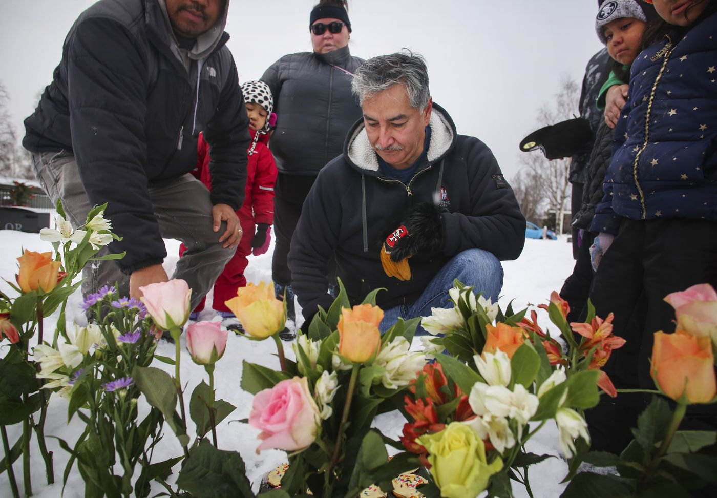 Scott Wells places a flower in the snow behind the grave marker for his partner, Amanda Bouffioux, as he and her family celebrate her birthday at the Anchorage Memorial Park Cemetery on Saturday, Dec. 26, 2020. Bouffioux tested positive for COVID-19 in August and spent three weeks on a ventilator before she died Sept. 8. The family celebrated by singing 'Happy Birthday ', eating cupcakes and listening to 'He Stopped Loving Her Today ', a song by Bouffioux's favorite singer, George Jones. The cupcakes were wrapped in her favorite color, purple. She would have turned 45 years old. (Emily Mesner / ADN)