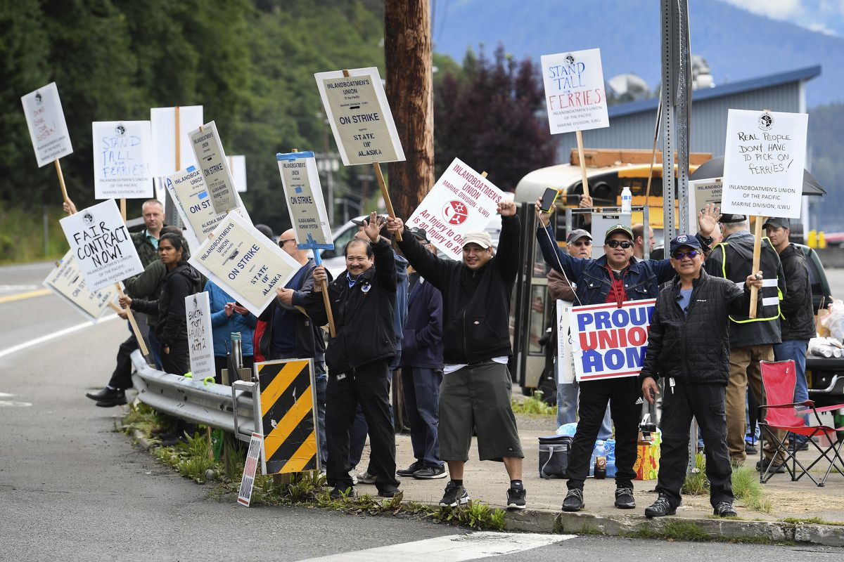Members of the Inland Boatmen's Union of the Pacific picket in front of the Auke Bay Terminal in Juneau, Alaska, Thursday, July 25, 2019. The union called a strike on Wednesday over failed negotiations with Gov. Mike Dunleavy's administration. State officials said Thursday more than $580,000 in fares has been refunded to passengers affected by striking ferry workers. (Michael Penn/The Juneau Empire via AP)