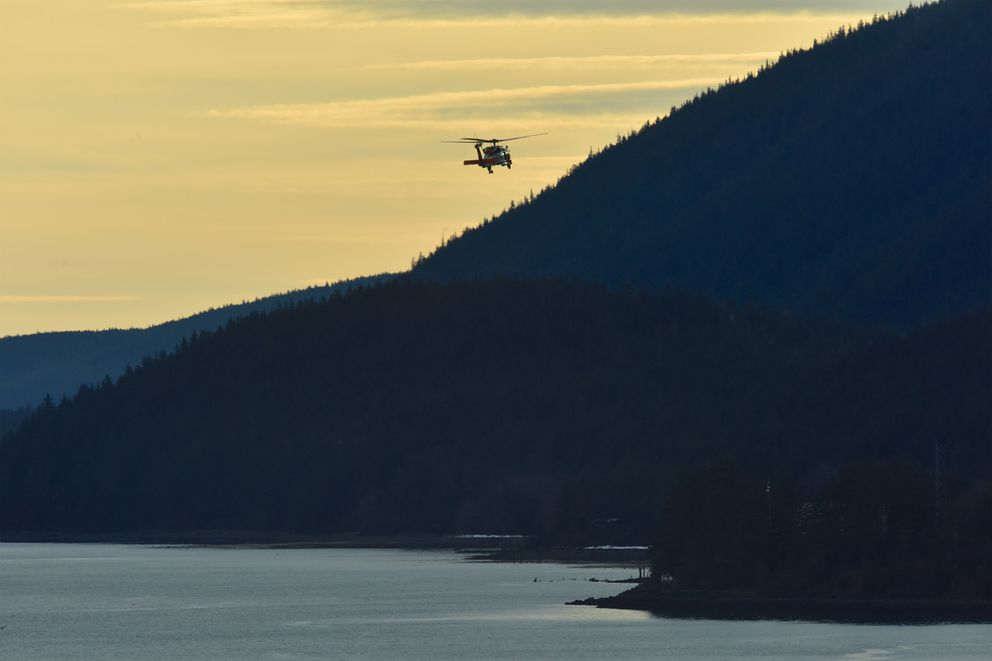A Coast Guard Air Station Sitka MH-60 Jayhawk helicopter crew searches Gastineau Channel in Juneau for two men in the water after their skiff capsized late Tuesday. (Jon-Paul Rios / U.S. Coast Guard)