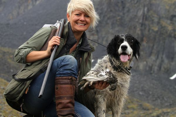 Author Christine Cunningham with her dog Winchester and the white-tailed ptarmigan they took on opening day of the bird hunting season last week (August 10, 2017). (Steve Meyer)
