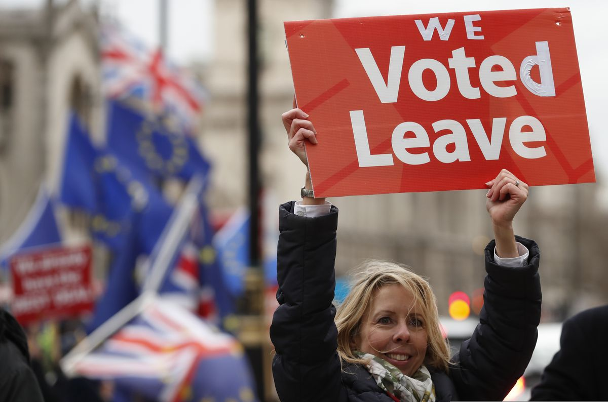 A pro-Brexit demonstrator waves a placard with others outside the Houses of Parliament in London Tuesday, Dec. 18, 2018. The British Cabinet was meeting Tuesday to discuss ramping up preparations for Britain's departure from the European Union without a deal, after Prime Minister Theresa May postponed Parliament's vote on her divorce agreement until mid-January. (AP Photo/Alastair Grant)