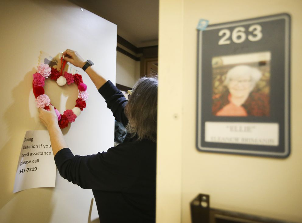 Winter Wolf hangs a Valentine's Day decoration on the door of her mother's room at the Anchorage Pioneer Home on Wednesday, Feb. 3, 2021. (Emily Mesner / ADN)