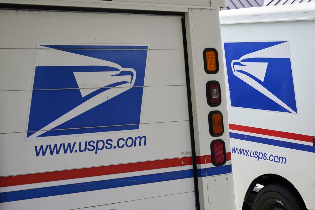 USPS mail delivery vehicles are parked outside a post office in Boys Town, Neb. (AP Photo/Nati Harnik, File)