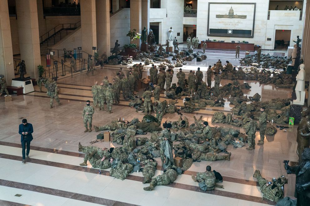 Members of the National Guard rest in the Capitol Visitors Center on Capitol Hill as the House of Representatives convene to impeach President Donald Trump, nearly a week after a pro-Trump insurrectionist mob breached the security of the nation's capitol while Congress voted to certify the 2020 election results on Wednesday, Jan. 13, 2021, in Washington, DC. (Kent Nishimura/Los Angeles Times/TNS)