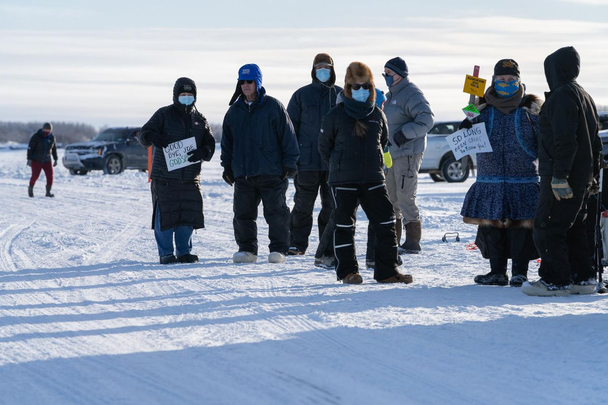 Friends of the late Joe Demantle Jr. wait for the procession carrying his body to drive onto the Kuskokwim River ice road in Bethel on Jan. 29 on the way to Tuluksak. (Katie Basile / KYUK)