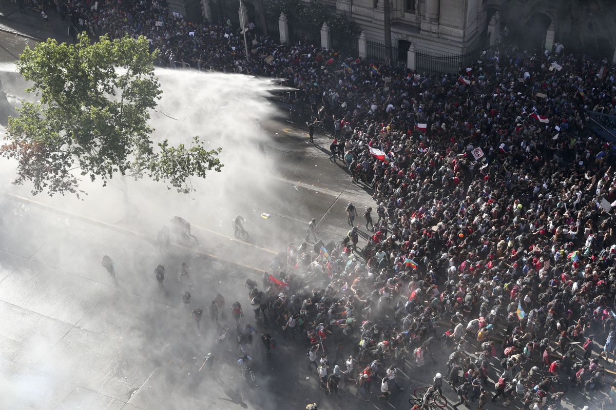 Police sprays water on anti-government demonstrators in Santiago, Chile, Monday, Oct. 28, 2019. President Sebastian Pinera announced changes in his cabinet in hopes of bringing peace back to the streets after days of protests that originally started over a hike in subway fares and have grown into a wider range of demands such as better pay, pensions, schools, housing and medical care.(AP Photo/Esteban Felix)