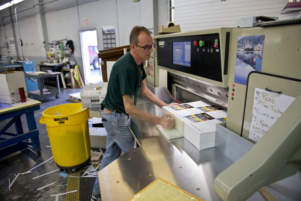 Lance Rome feeds stacks of printed materials into a trimming machine at Northern Printing. Rome works two jobs, one as a bartender at the Anchorage Museum and another as a machine operator for Northern Printing. (Marc Lester / Alaska Dispatch News)