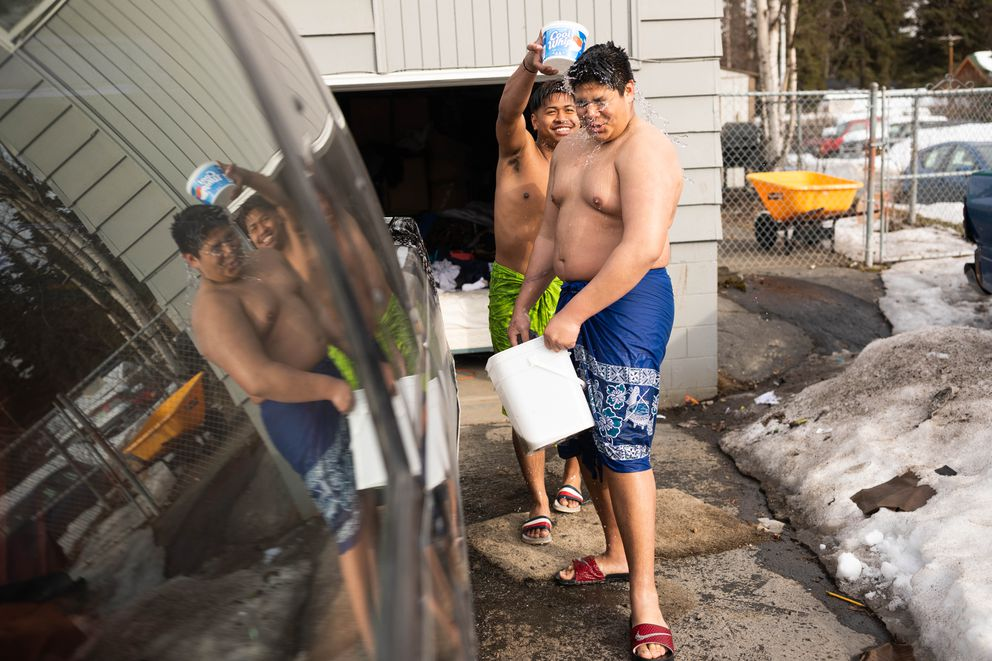 Faitete Pefua dumps water on his cousin Lance Pefua as they wash a family car Friday, April 6, 2018 in Turnagain. The cousins, who recently moved to Alaska from Hawaii, are wearing ie lavalava, a traditional Polynesian dress. (Loren Holmes / ADN)