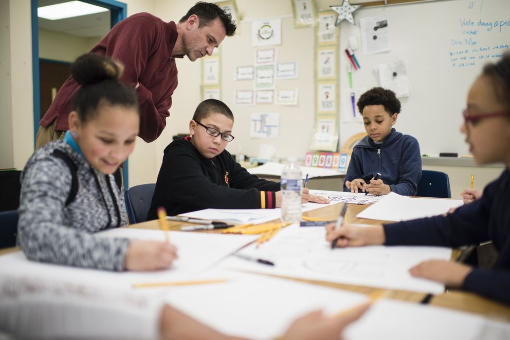 Craig Sampsell with his fifth-grade students, making posters for a walk out protesting gun violence, at Case Elementary School in Akron, Ohio, March 12, 2018. Many districts and schools that are tolerating, if not encouraging, participation in the planned national walkout are also calibrating their approach for their youngest students. (Dustin Franz/The New York Times)