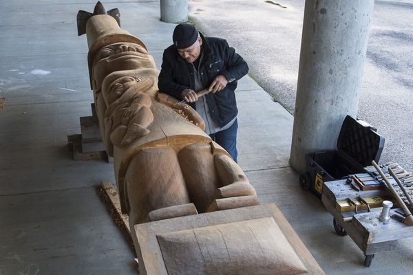 In this photo taken Oct. 31, 2018, Wayne Price, master Tlingit carver and Associate Professor of Northwest Coast Arts and Sciences, works on a healing pole at the University of Alaska Southeast in Juneau, Alaska. The pole will be erected with a screen at AWARE's women's transitional housing at Twin Lakes in April. (Michael Penn/Juneau Empire via AP)