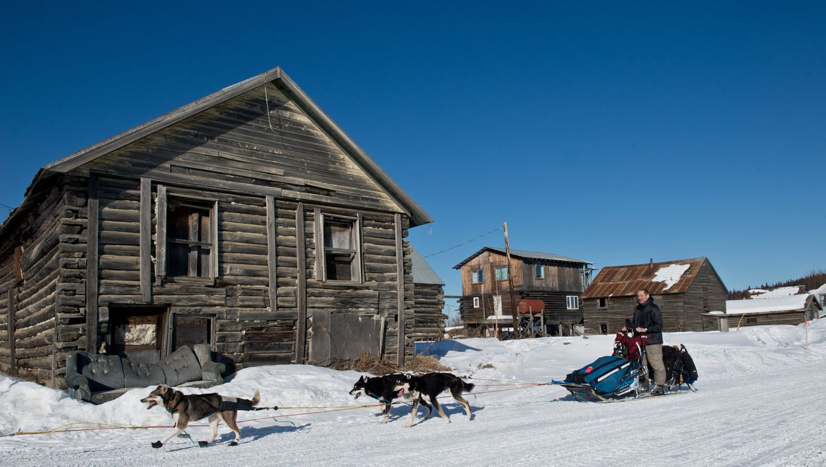 Iditarod musher Ketil Reitan passes buildings in Nulato on his way to the checkpoint in2016. (Marc Lester / Alaska Dispatch News)