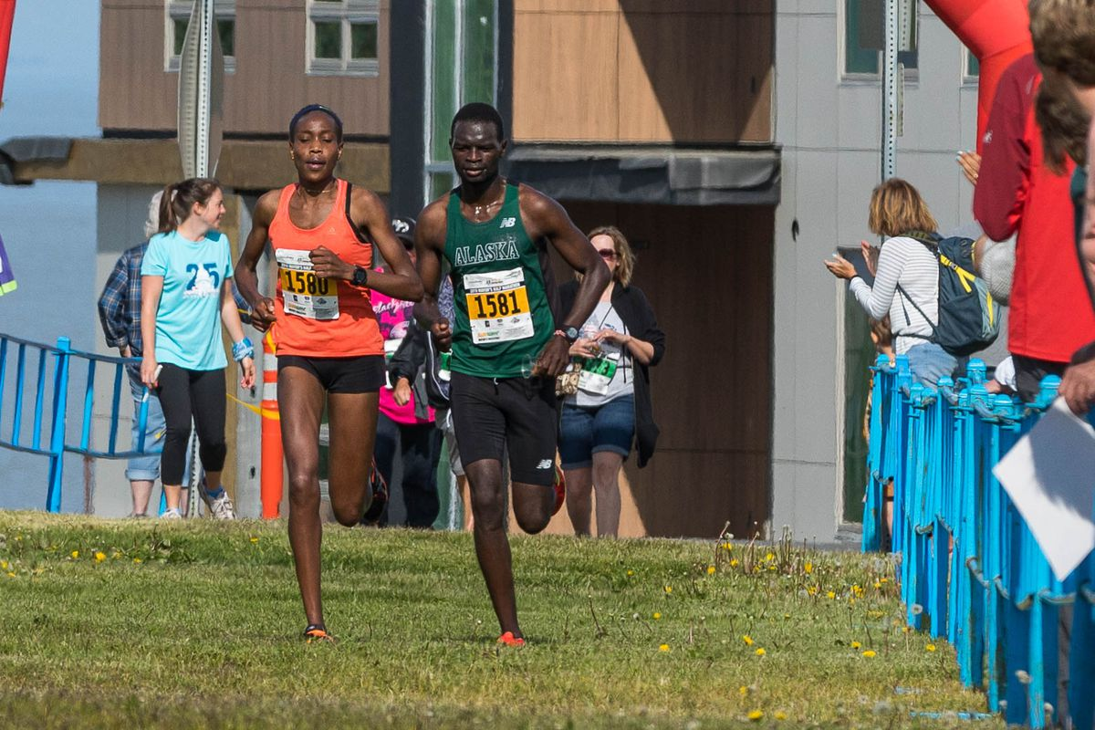 Caroline Kurgat and Felix Kemboi raced toward the finish line of the Mayor's Half Marathon. Kurgat finished first overall, shattering the previous women's course record by more than five minutes. (Loren Holmes / ADN)