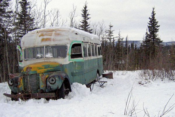 FILE - This March 21, 2006, file photo, shows the abandoned bus where Christopher McCandless starved to death in 1992 on Stampede Road near Healy, Alaska. For more than a quarter-century, the old bus abandoned in Alaska's punishing wilderness has drawn adventurers seeking to retrace the steps of a young idealist who met a tragic death in the derelict vehicle. Scores of travelers following his journey along the Stampede Trail have been rescued and others have died in the harsh back-country terrain. Now families of some of those who died are proposing looking at building a footbridge over the Teklanika River. (AP Photo/Jillian Rogers, File )