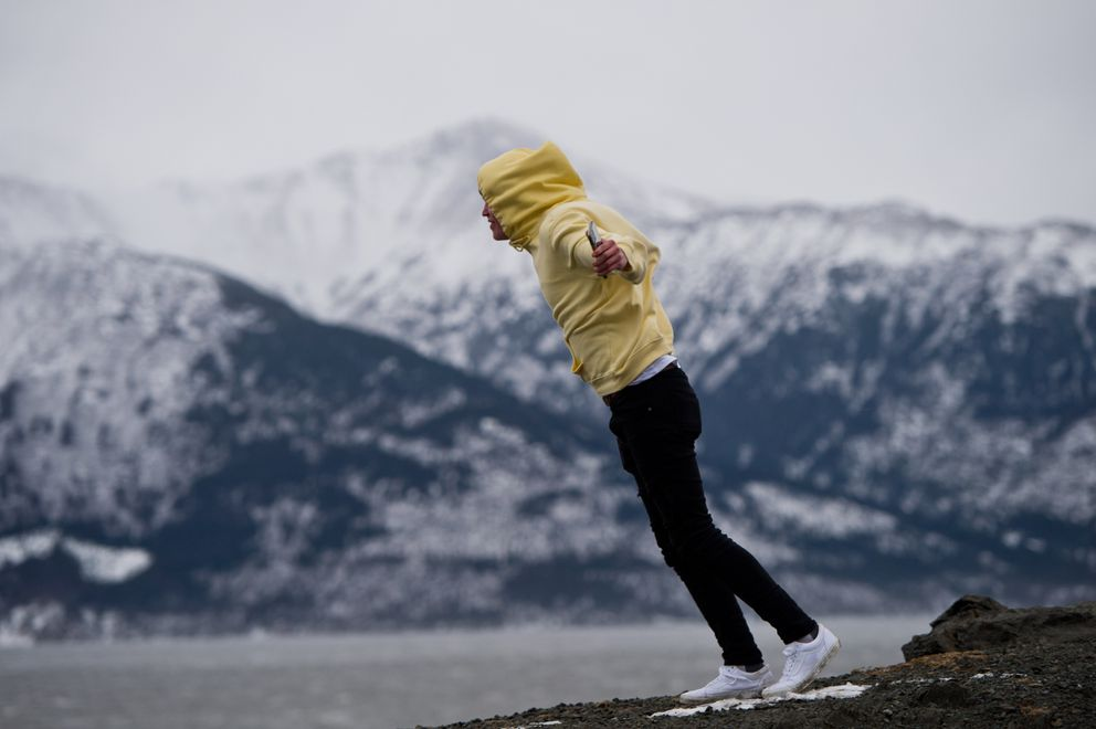 Sam Wirtanen leans into strong wind during a brief stop at Beluga Point on Turnagain Arm on Monday, February 17, 2020. Wirtanen and several others from the Palmer area were returning from a day skiing at Alyeska on Monday. (Marc Lester / ADN)