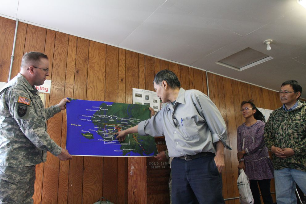 Command Sgt. Maj. Richard Hildreth of the Alaska National Guard helps to hold a map as Boris Epchook — who served as a Guard noncommissioned training officer for a Kwethluk unit in the 1980s — points out village detachments on Tuesday, June 7, 2016, during a meeting in the village with Asst. Army Sec. Debra Wada. (Lisa Demer / Alaska Dispatch News)