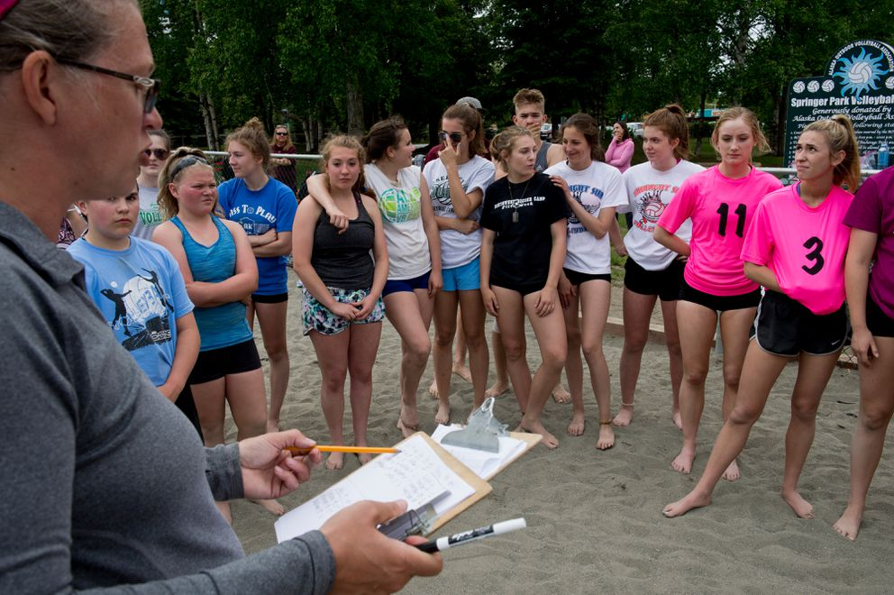 Erica Johnson, left, talks to Pass To Play AK beach volleyball tournament players on Friday. Pass To Play hosts several tournaments in the summer in addition to its camps. (Marc Lester / Alaska Dispatch News)