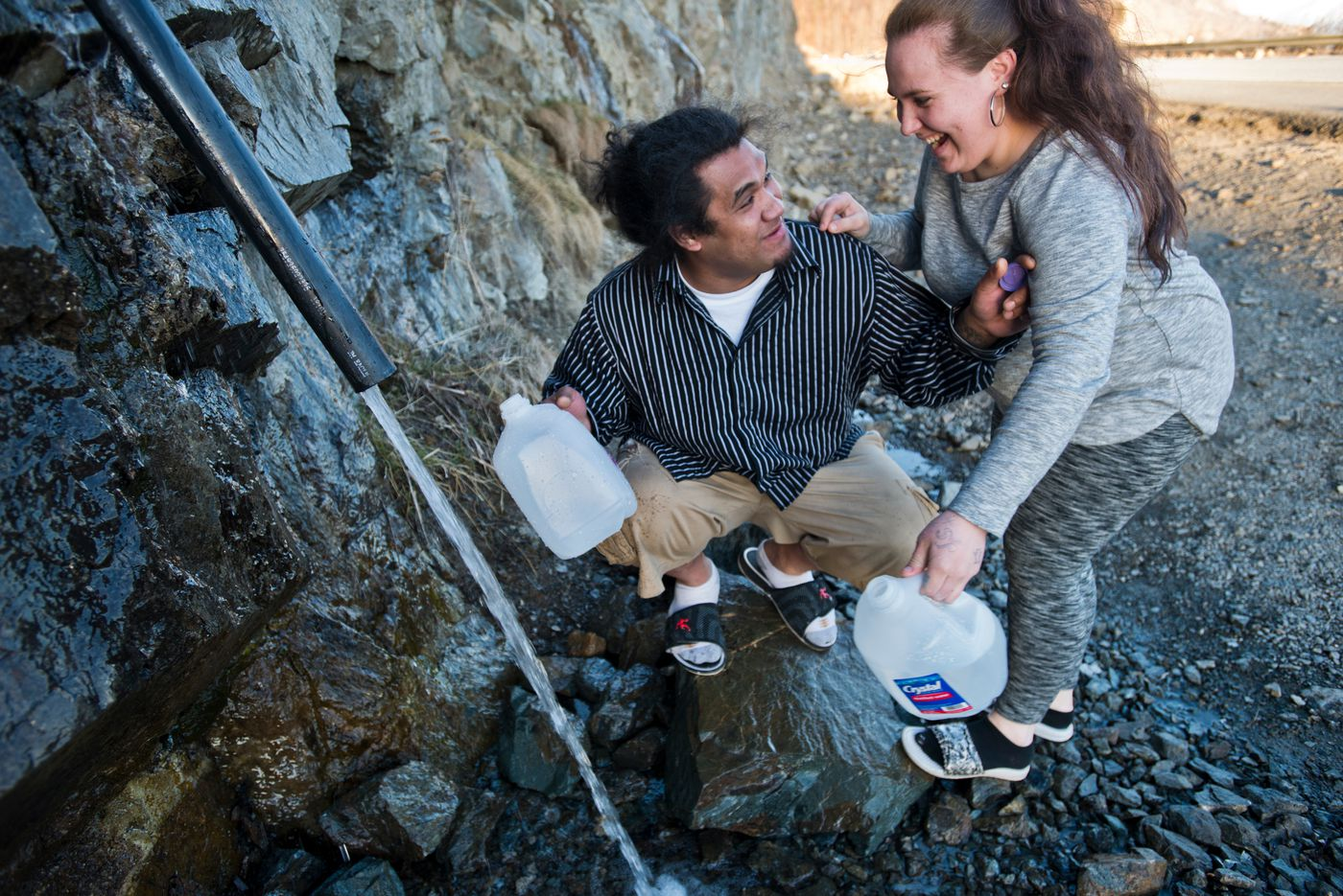 Paypay Oloi and Amelia Reed say they make the trip regularly to collect water from the pipe sticking out of the rocks at Mile 109 of the Seward Highway. They each filled 1-gallon jugs. (Marc Lester / Alaska Dispatch News)
