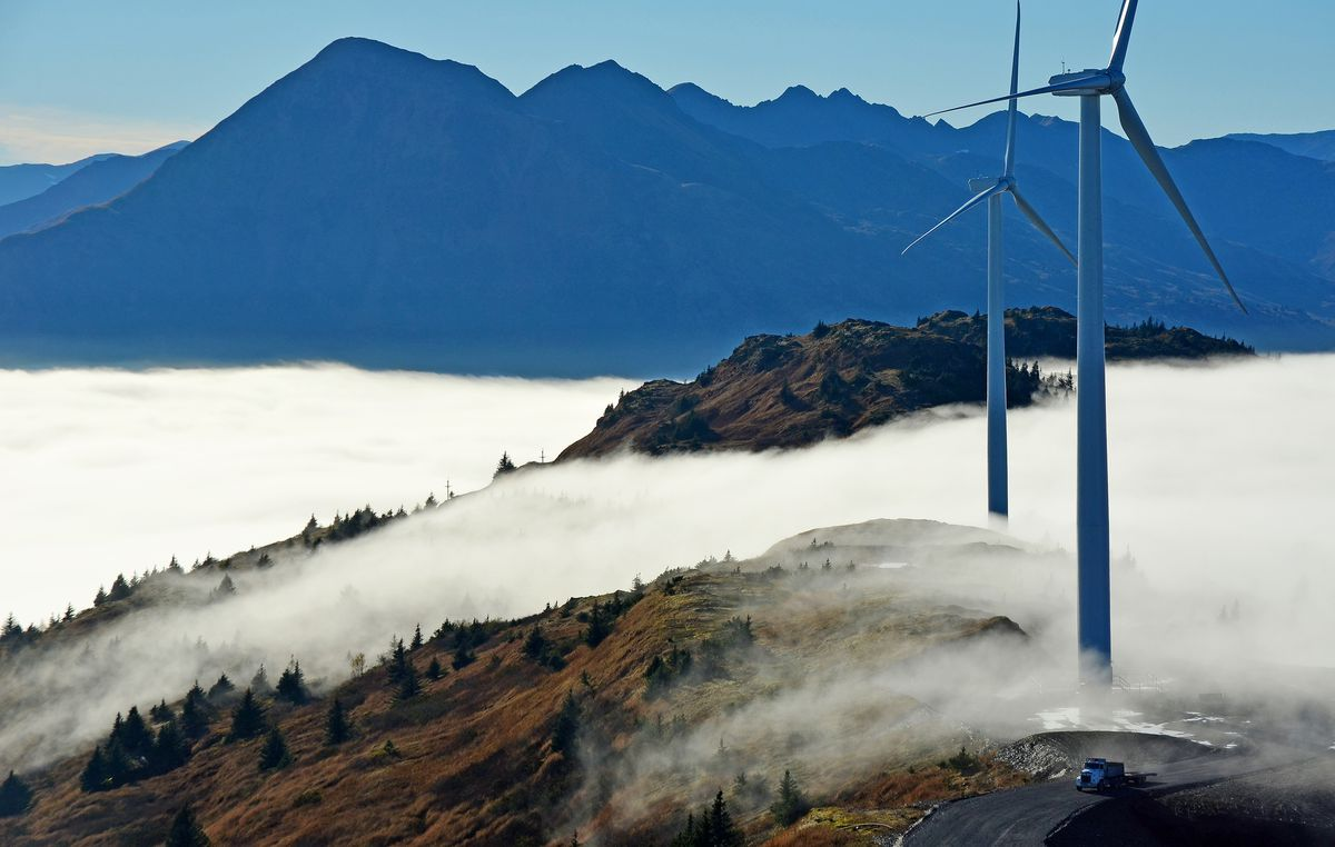 Two wind turbines jut from a sea of clouds atop Kodiak, Alaska's Pillar Mountain.   (James Brooks)