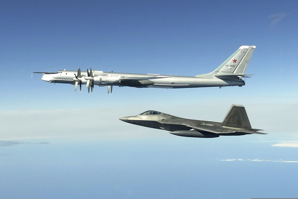 In this image taken Tuesday, June 16, 2020, and released by the North American Aerospace Defense Command, a Russian Tu-95 bomber, top, is intercepted by a U.S. F-22 Raptor fighter off the coast of Alaska. (North American Aerospace Defense Command via AP)