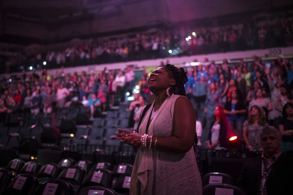 """Faitth Brooks worships through song during a """"BELONG Tour"""" event, which serves as a gathering for women who crave a deeper connection with each other, at the University of South Florida Sun Dome in Tampa, Fla., Oct. 14, 2016. (Loren Elliott/The New York Times)"""