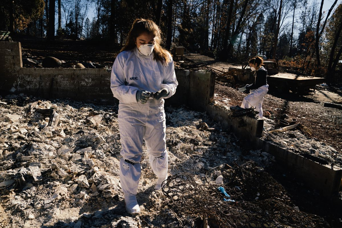 Jade Ryan, left, and Jasmine Ryan sift through the remains of their home, destroyed by the Camp Fire that swept through Paradise, California. Their parents, unable to purchase a home nearby, moved to South Carolina to be closer to family. The girls are staying with a family friend while they attend school. (Photo by Mason Trinca for The Washington Post)