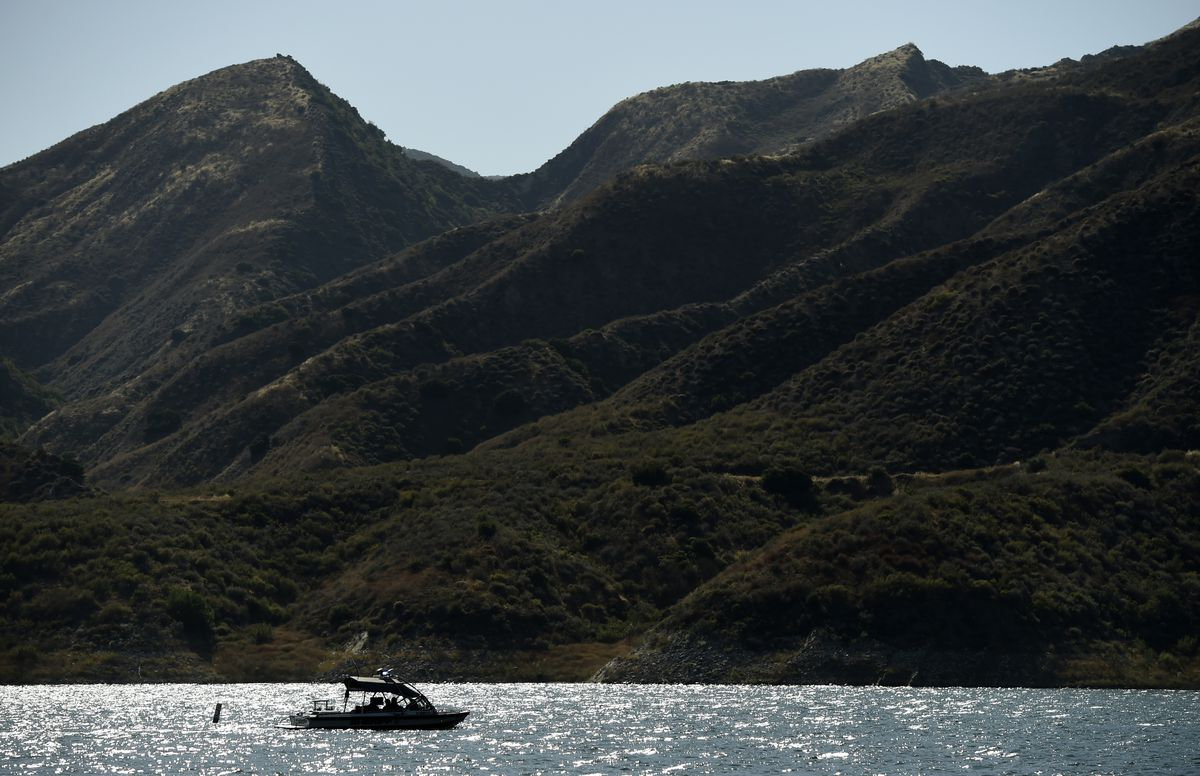A search-and-rescue boat looks for missing actress Naya Rivera at Lake Piru, Friday, July 10, 2020, in Los Padres National Forest, Calif., about 55 miles (90 kilometers) northwest of Los Angeles. (AP Photo/Chris Pizzello)