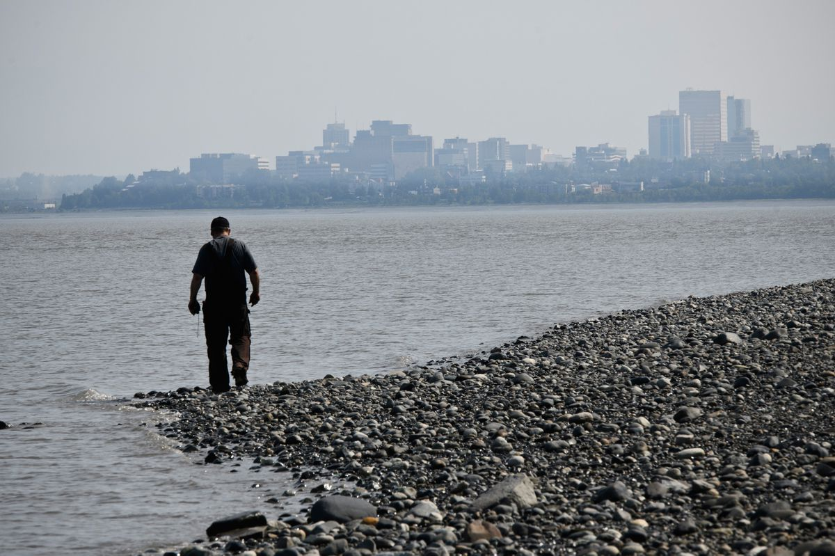 Smoky air limits the view from the beach near Point Woronzof, where a man walks the shoreline on June 27, 2019. (Marc Lester / ADN)