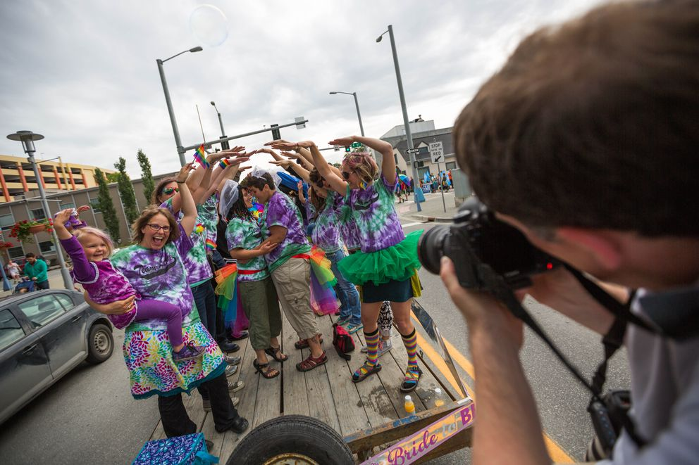 Photographer Jonathan Gurry makes a photo of brides-to-be KT Latico, left, and Marisa Latico during the Alaska PrideFest parade in downtown Anchorage on Saturday, Jun. 25, 2016. The couple will marry Saturday afternoon at the Alaska Native Heritage Center. (Loren Holmes / Alaska Dispatch News)