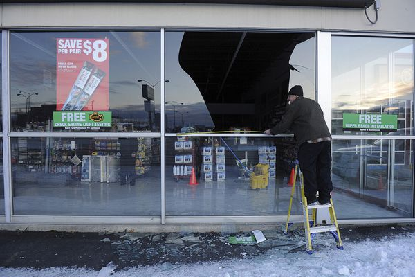FILE - In this Nov. 30, 2018, file photo, Dennis Keeling, of Instant Services, measures for a broken window at an auto parts store following an earthquake in Anchorage, Alaska Seven weeks after the massive earthquake struck Alaska, the seemingly endless aftershocks are keeping many residents filled with anxiety. (AP Photo/Mike Dinneen, file)