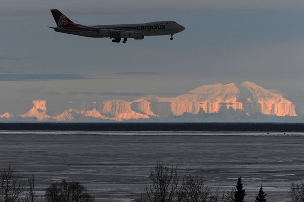 A Boeing 747 lands at Ted Stevens Anchorage International Airport on Wednesday, Jan. 16, 2019, as a Fata Morgana mirage distorts Mount Foraker and mountains in the Alaska Range. The optical phenomenon occurs as rays of light are bent as they pass through layers of warm air above significantly colder air near the ground during a thermal inversion. (Bill Roth/ ADN)