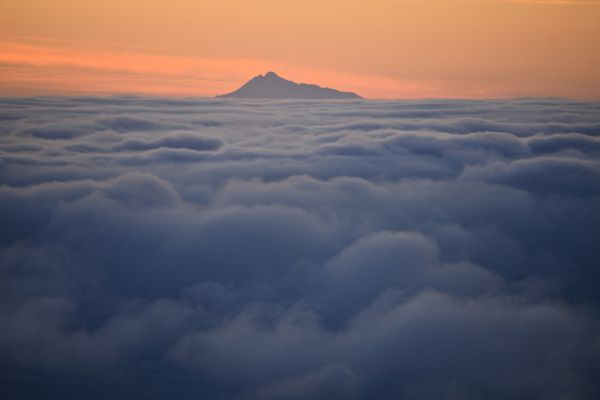 Mount Redoubt, a 10,197-foot volcano, is visible beyond clouds in the Anchorage area on February 6, 2021. (Marc Lester / ADN)