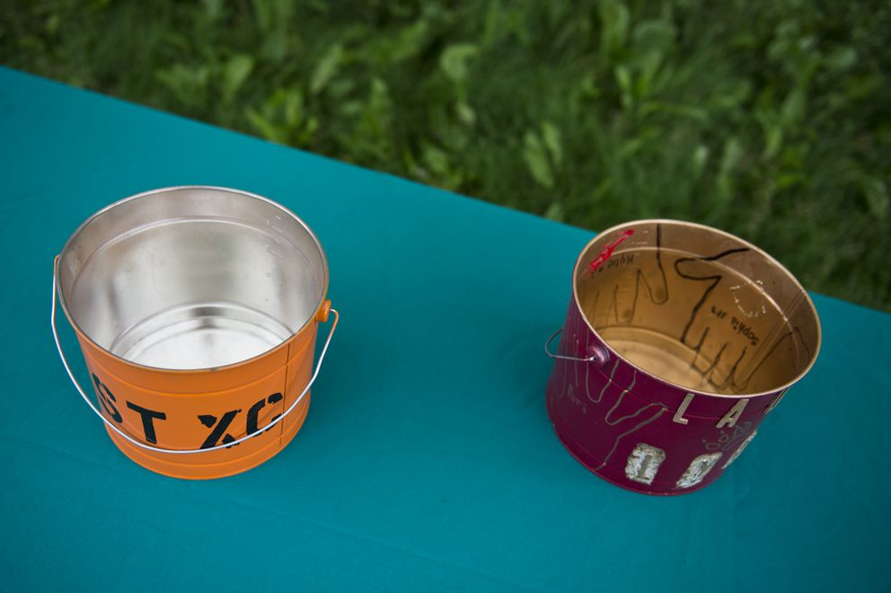 Buckets that teams get to paint in school colors are the prizes in the annual dual meet between West and Dimond. (Marc Lester / ADN)