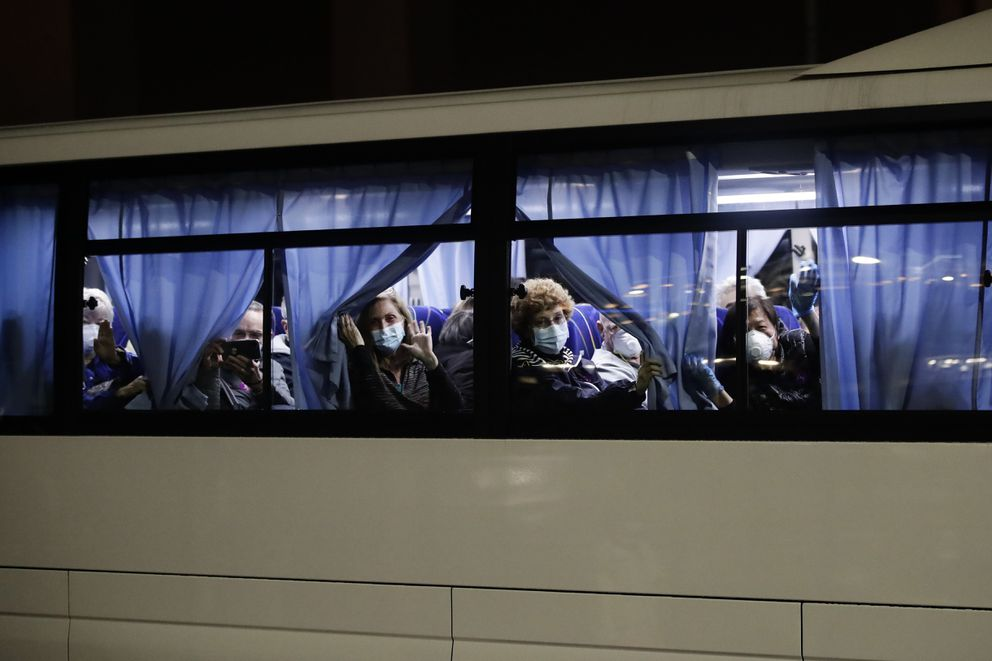 Buses carrying passengers from the quarantined Diamond Princess cruise ship leave a port in Yokohama, near Tokyo, Monday, Feb. 17, 2020. A group of Americans cut short a 14-day quarantine on the Diamond Princess cruise ship in the port of Yokohama, near Tokyo, to be whisked back to America. But they will have to spend another quarantine period at a U.S. military facility to make sure they don't have the new virus that's been sweeping across Asia. (AP Photo/Jae C. Hong)